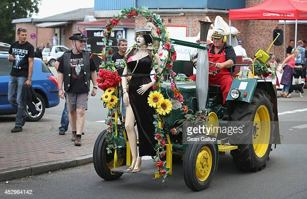 A man driving a decorated tractor passes by festivalgoers on the village main street outside the 2014 Wacken Open Air heavy metal music festival on...