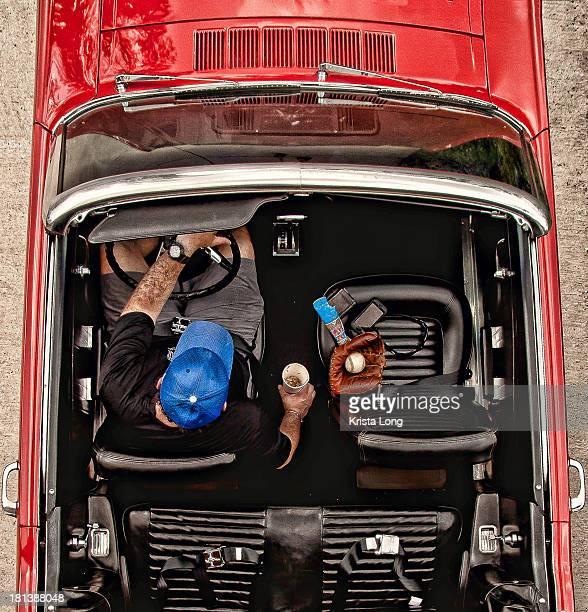 A man driving a red convertible car