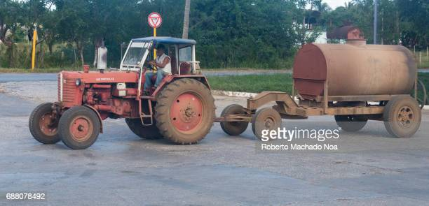 Man driving a Russian tractor attached to a large tank across the road Cuban real people everyday lifestyle and transportation