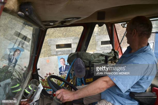 TOPSHOT A man driving a tractor looks at electoral posters of candidates for the upcoming French parliamentary elections on May 29 2017 in Nauvay...