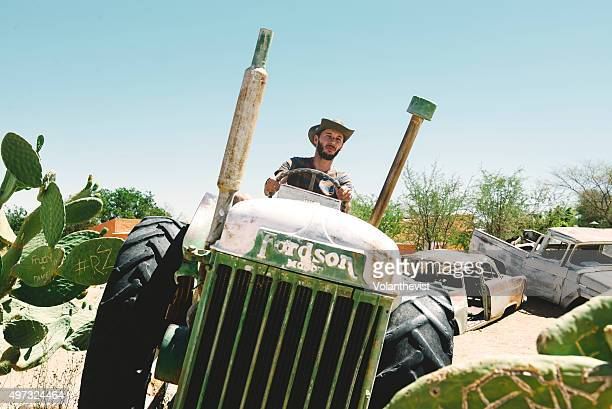 Man driving an abandoned tractor on the Namib desert, Solitaire, Namibia