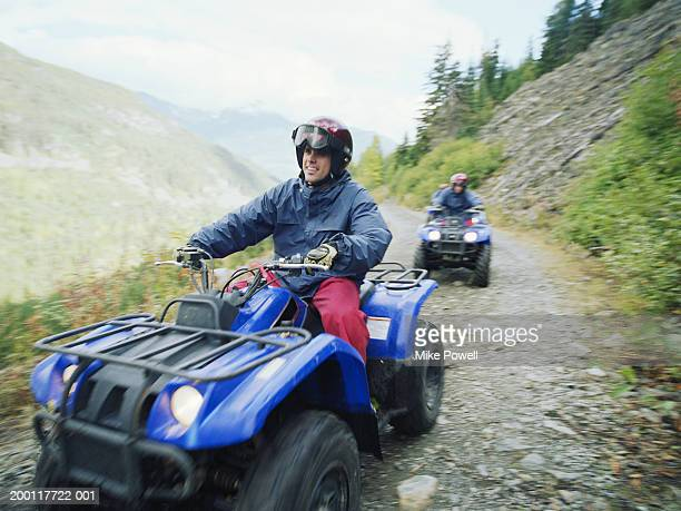 Man driving ATV with group on mountain road, (focus on man)