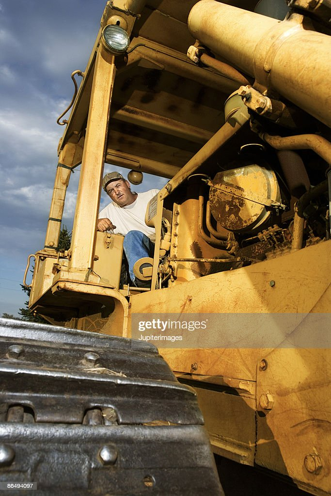 Man On Bulldozer : Man driving bulldozer stock photo getty images
