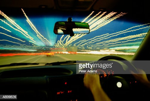 man driving car at night view from inside stock photo