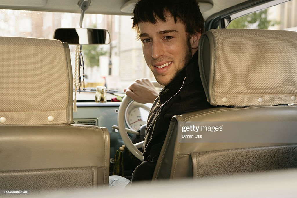 Man driving car, looking over shoulder, smiling, portrait : Stock Photo