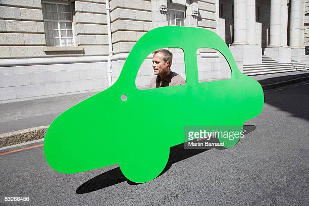 Man driving car outline on urban roadway