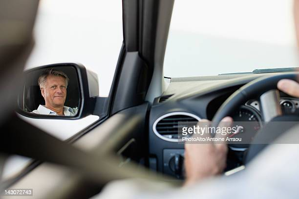 Man driving car, reflected in driver's side mirror