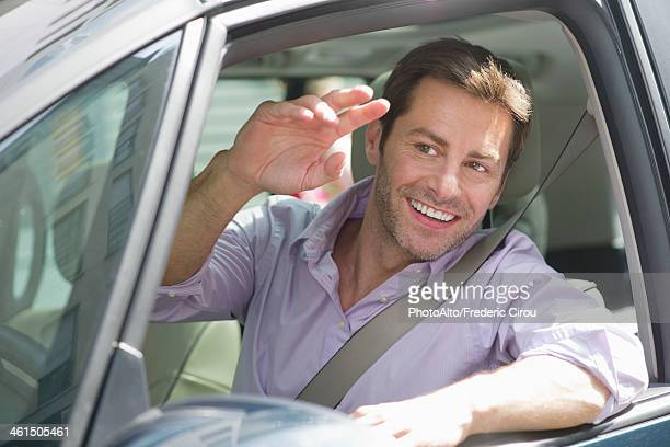 Man driving car, smiling out window and waving