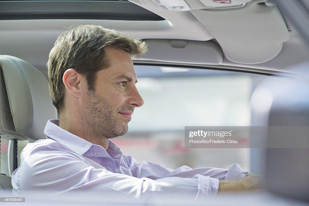 Man driving car, smiling