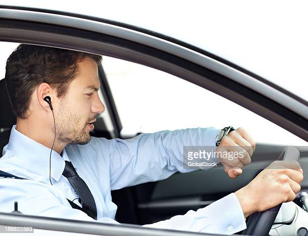 Man driving car with earphones on, looking at wrist watch