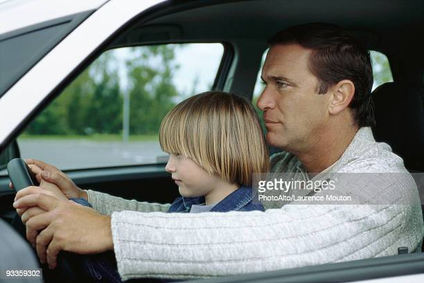 Man driving car with young son sitting on lap, both holding steering wheel