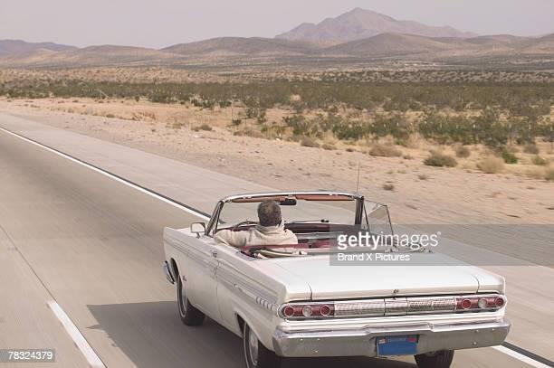 Man driving convertible along desert road