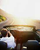Man driving convertible car along ocean highway at sunrise, elevated view