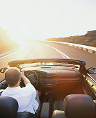 Man driving convertible car on highway, rear view