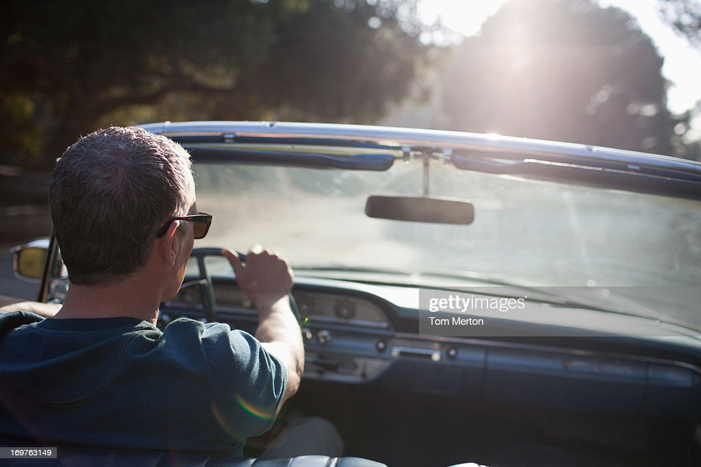 Man driving convertible car : Stock Photo