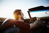 Man driving convertible in desert at sunset