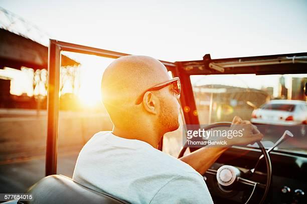 Man driving convertible on summer evening