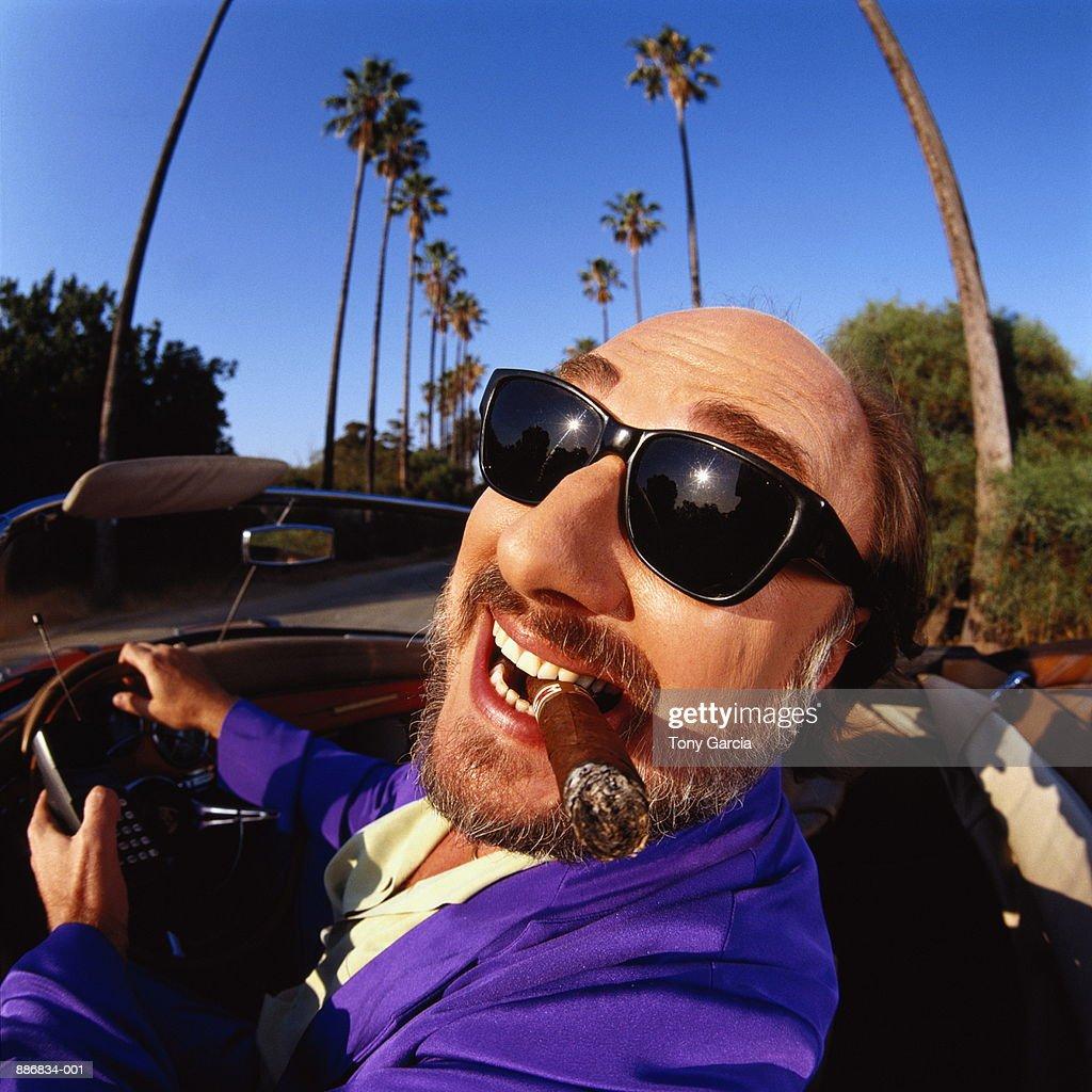 Man driving convertible, smoking cigar, California, USA (wide angle)