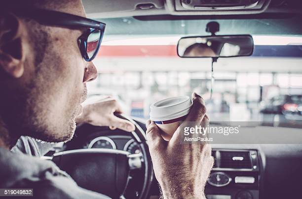 Man driving his Car and drinking take away coffee