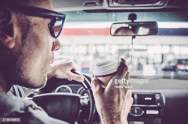 Homme au volant d'un véhicule et de boire du café à emporter