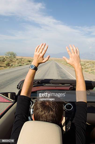 Man driving in convertible with arms raised