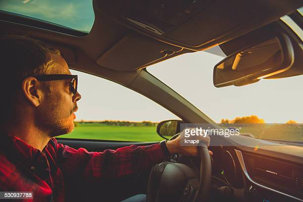 Man driving in sunset