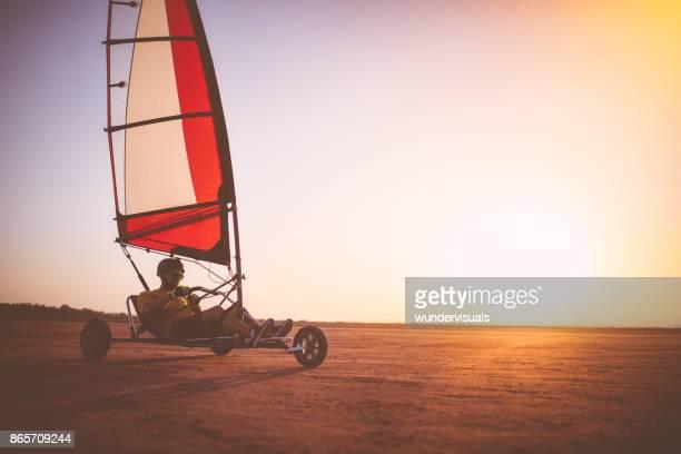 Man van drijvende land zeilen blokart op het strand bij zonsondergang