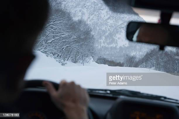 Man driving on snow covered road, Lofoten Islands, Norway