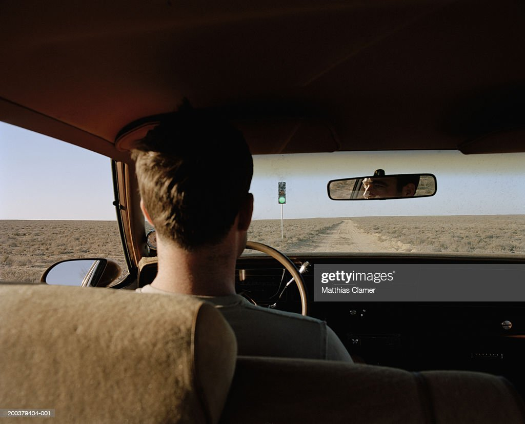 Man driving past traffic light on desert road, rear view, close-up