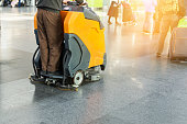 Man driving professional floor cleaning machine at airport or railway station.  Floor care and cleaning service agency.