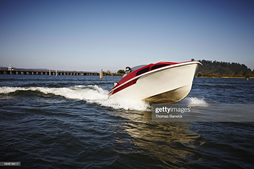 Man driving small power boat across water