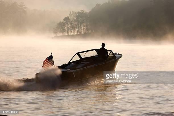 Man driving speedboat alone on hazy foggy lake at dawn