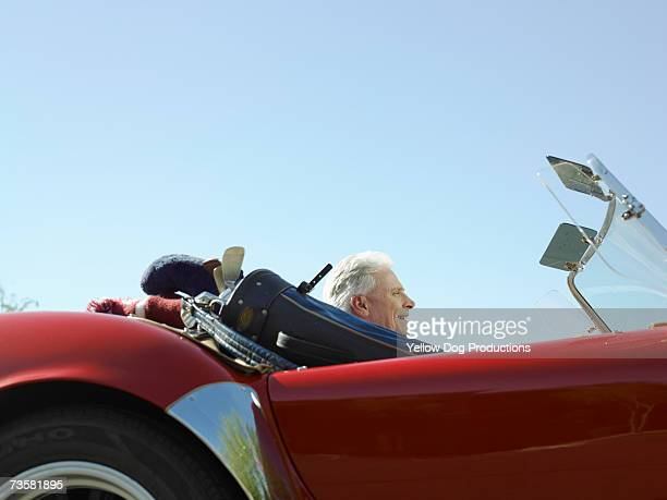 Man driving sport car with golf bag inside, side view
