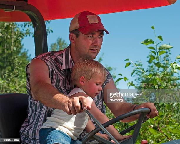 man driving tractor with his son