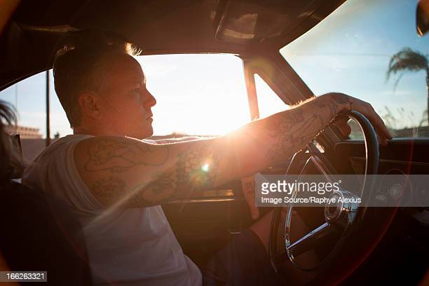 Man driving vintage car at sunset