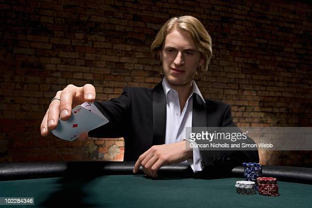Man dropping cards on table in casino