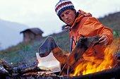 Man drying socks by campfire
