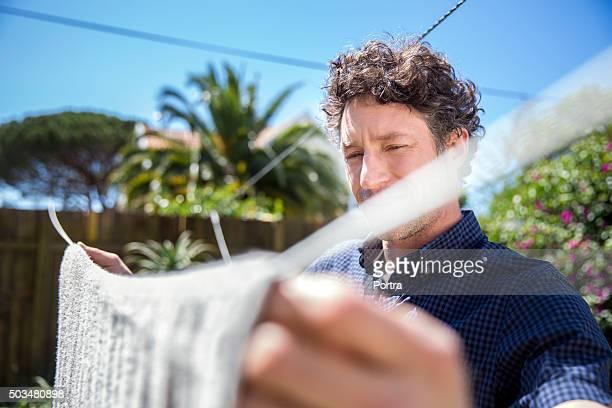 Man drying towel in yard