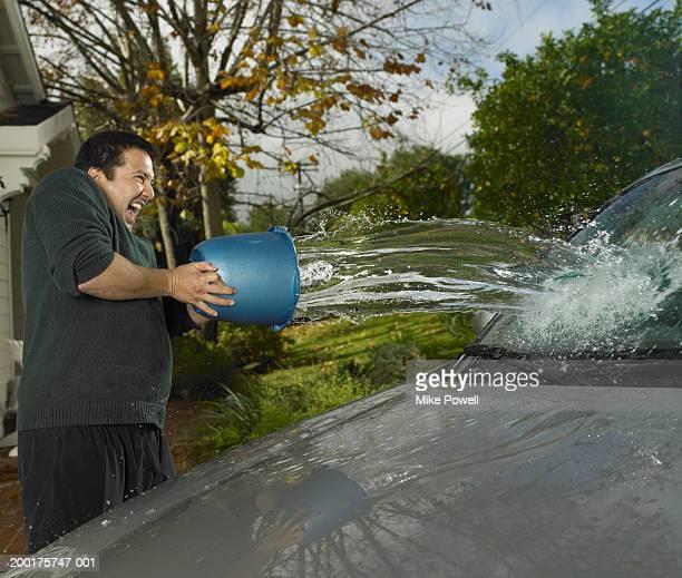 Man dumping bucket of water on car in driveway