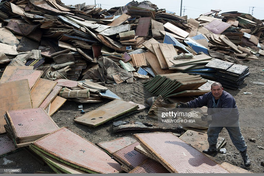 A man dumps saturated tatami mats at a temporary dumping ground following the tsunami in Higashimatsushima, Miyagi prefecture on March 31, 2011. The number of confirmed dead and people listed as missing from the earthquake and tsunami that devastated Japan's northeast coast topped 28,000 on March 28.