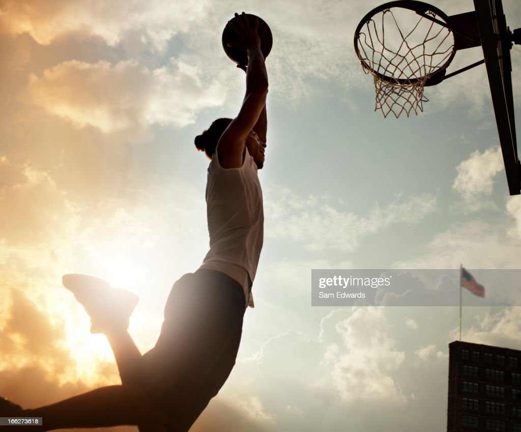 Man dunking basketball on court