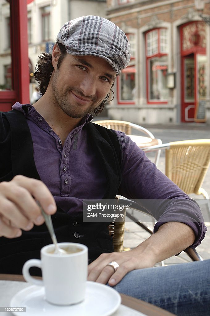Man, early 30s, wearing casual clothes sitting in an outdoor café stirring a coffee cup, smiling