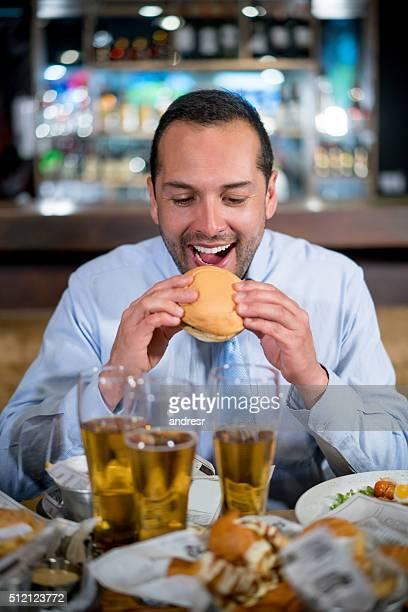 Man eating a burger at a bar
