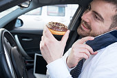Man eating a doughnut and talking on the phone driving his car