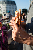closeup of a caucasian man, wearing a t-shirt, eating a ham sandwich, made with a german Laugenstange roll, on the street