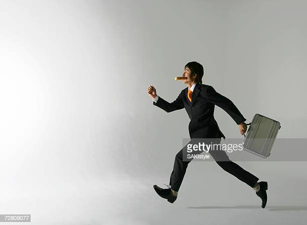 Man eating a piece of bread , running