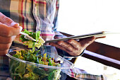 closeup of a young caucasian man wearing a plaid shirt eating a prepared salad while is using his digital tablet