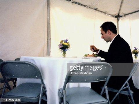 Man eating alone in banquet tent : Stock Photo