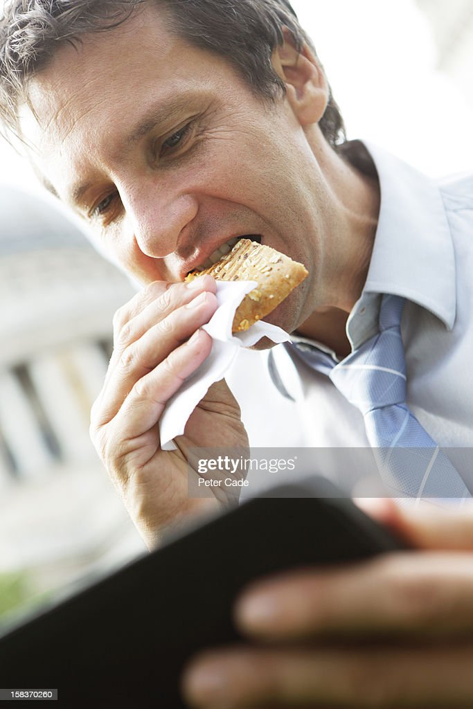Man eating and looking at computer tablet : Stock Photo