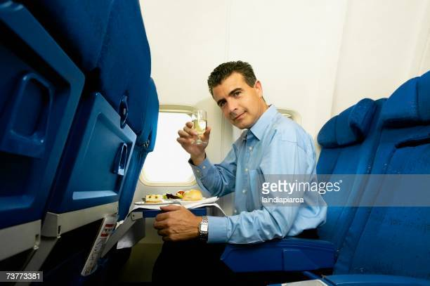 Man eating and toasting with wine on airplane